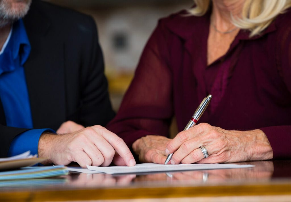 A woman signing her will