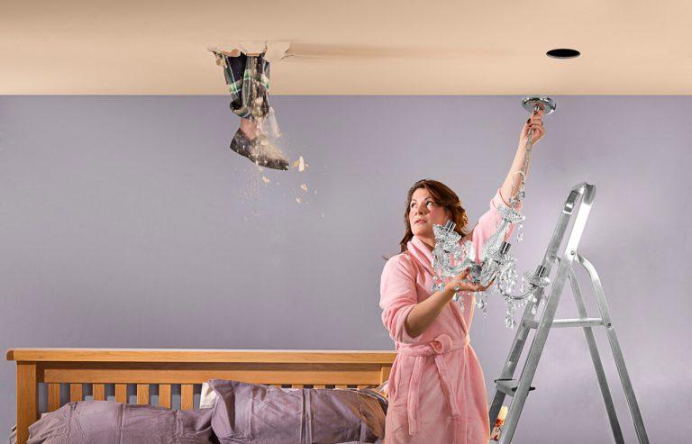 Man's foot coming through bedroom ceiling