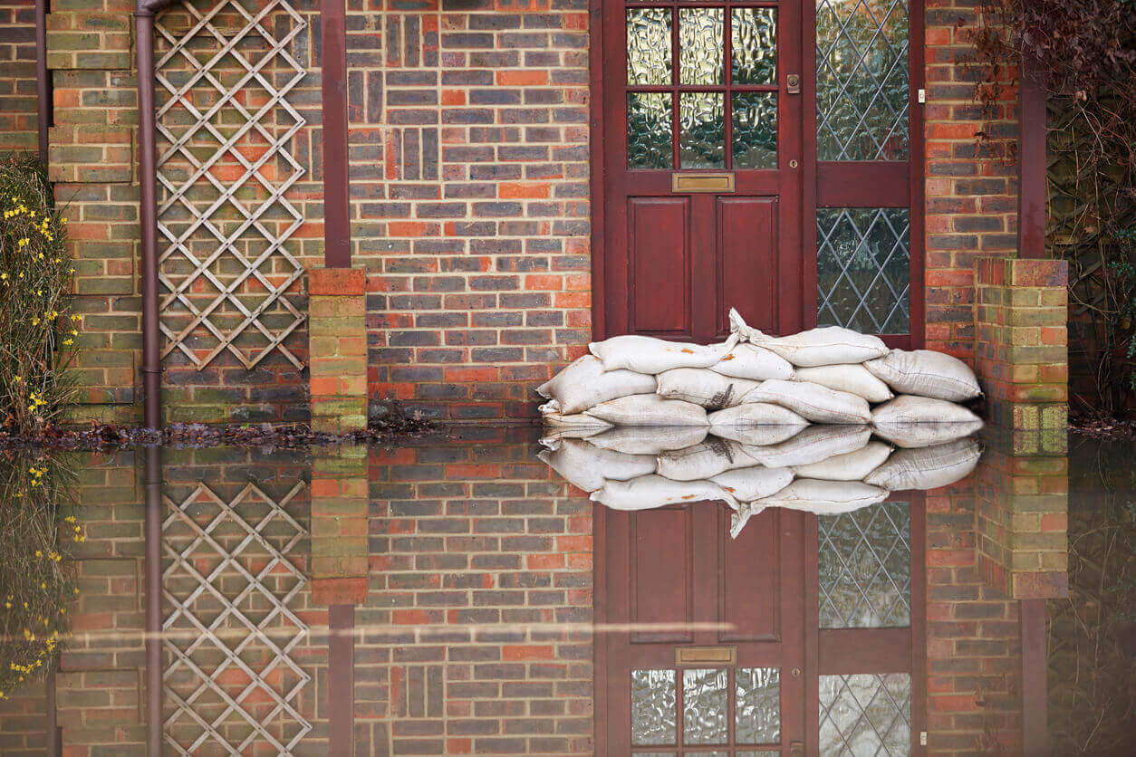 A house affected by flooding with sandbags by the front door