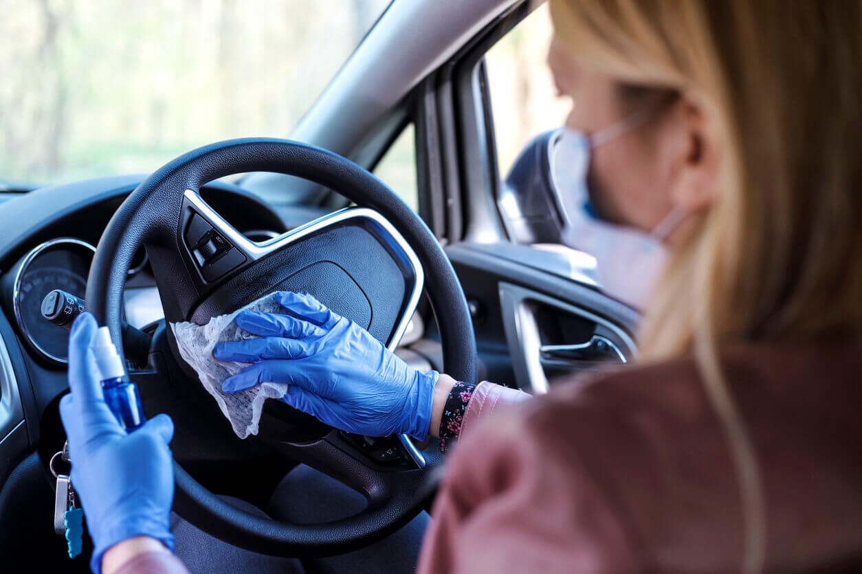 Cleaning steering wheel of financed car with wipe and gloves