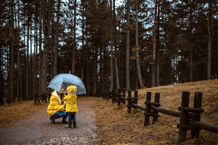 mother protecting child from rain with umbrella