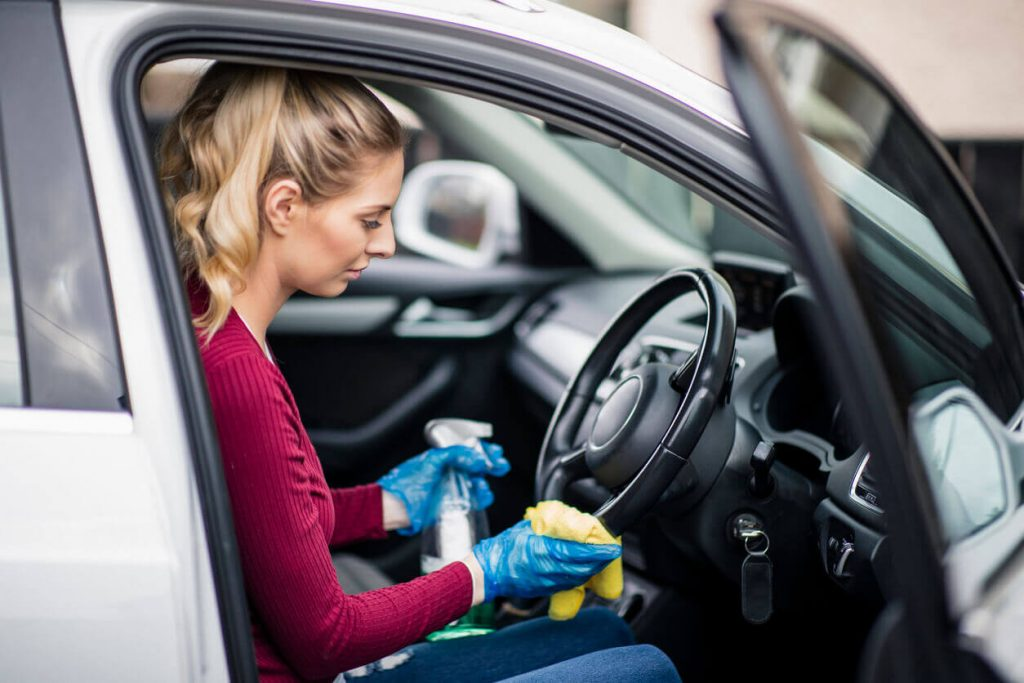 A woman cleaning inside her car