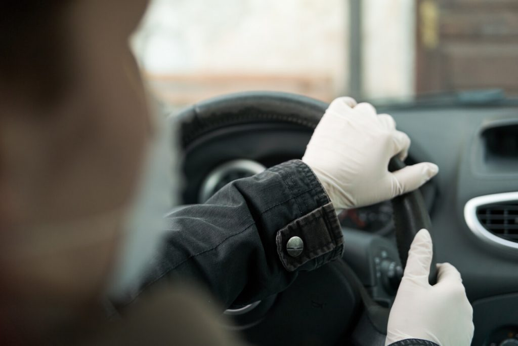 A person with a face mask and gloves on and holding the steering wheel