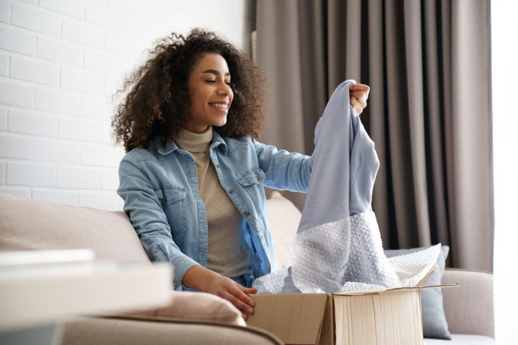 A woman looking happy while opening a package