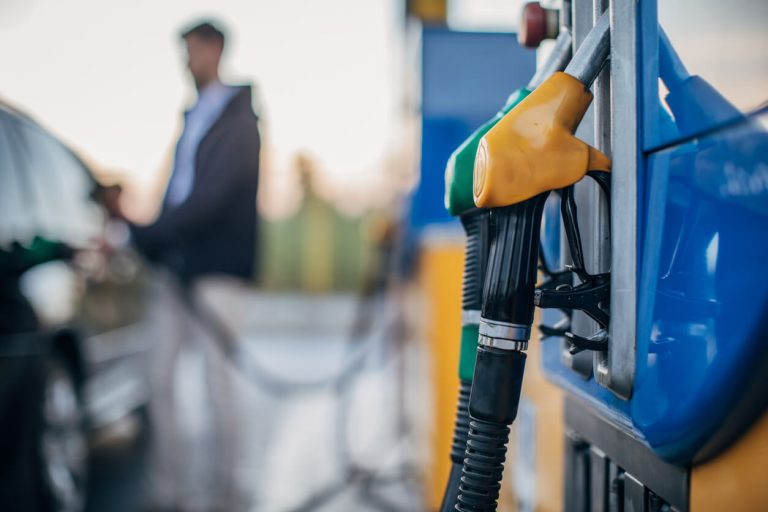 A close up of petrol and diesel pumps next to a man filling up his tank