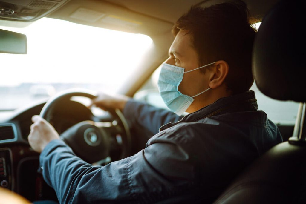 A man driving his car with a face mask on