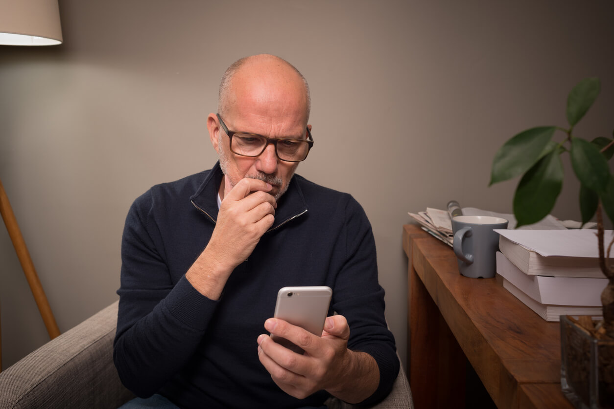 A man looking worried at his phone