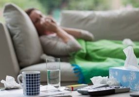 Ill woman on the sofa with medicine and tissues around her.