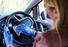 A woman wearing a mask and clearing her steering wheel