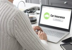 A woman on her laptop looking at car insurance quotes