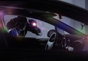 car thief looking in car with flashlight