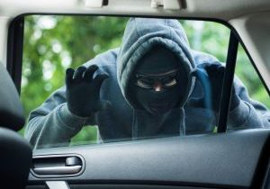 Thief with hood looking into car window