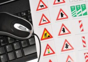 Road signs on paper next to a keyboard and mouse