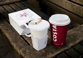 A cup of Costa coffee next to lunch and cigarette