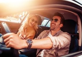 A couple laughing in the car while driving