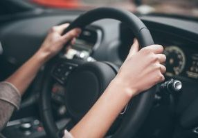 Close up of person holding a steering wheel