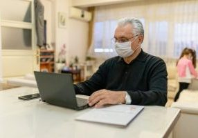 Ill man with mask on working from home