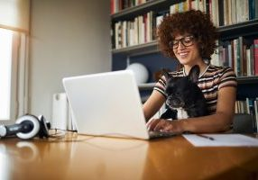 Woman working from home on her laptop with her dog on her lap.
