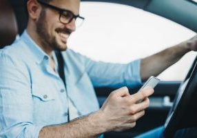 man on mobile phone while driving car