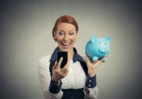 woman smiling whilst holding mobile phone and blue piggy bank
