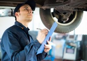 mechanic inspecting car during MOT test