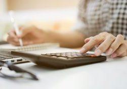 A man calculating his car insurance at desk